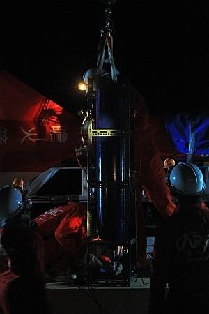 正在為火箭換裝笑氣的鋼瓶,要灌入將近100 公斤的笑氣。成員退到離火箭二三十公尺遠的空地邊界,監看螢幕轉播灌氣過程與鋼瓶重量。