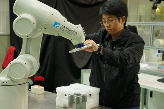 人拉著機械手臂上的握把(握把上視零件種類安裝不同夾爪),將它推至零件面前、按下按鈕使其夾取零件、再帶著機械臂到另一個地方放下零件,機器人會記下這整套動作與軌跡。