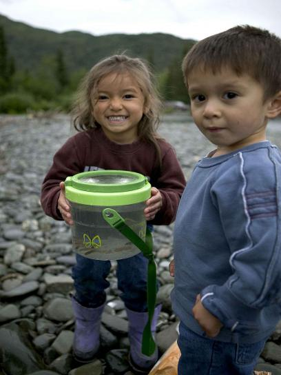 two-young-children-enjoying-a-day-of-fishing-on-a-river-408x544
